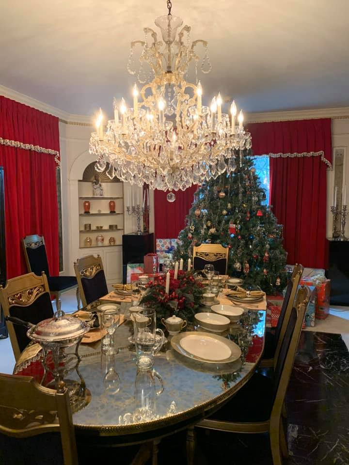 Graceland's dining room table, set for a Christmas dinner, complete with a Christmas tree.